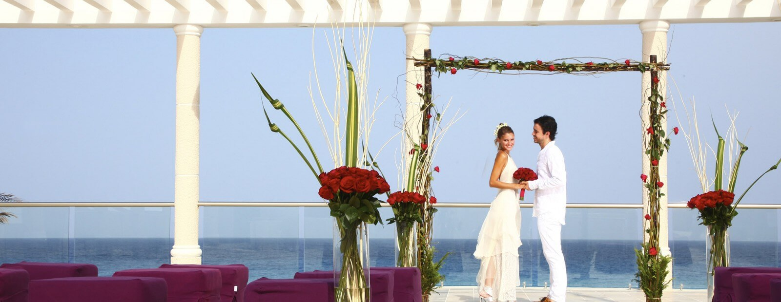 A couple getting married with the scarlet love wedding setting in Sandos Cancun